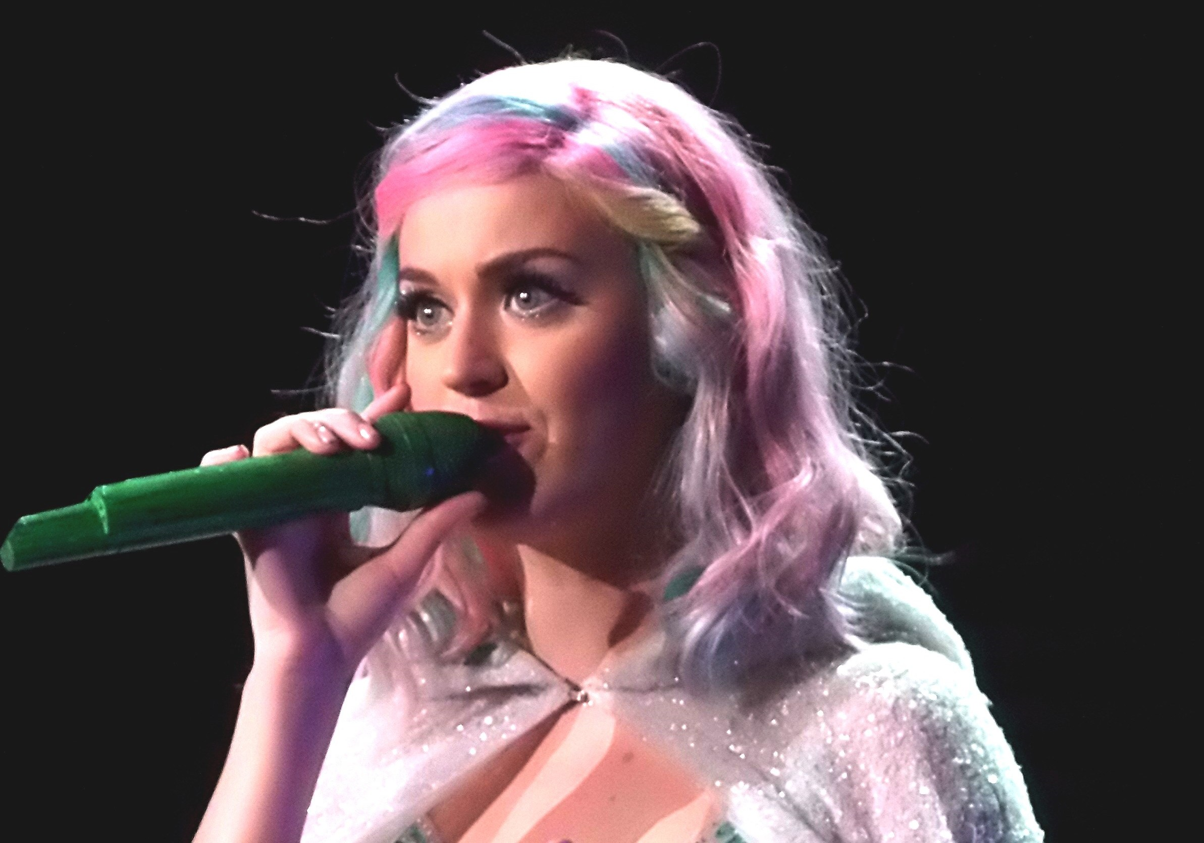 katy perry singing into a microphone while wearing a multicolor outfit